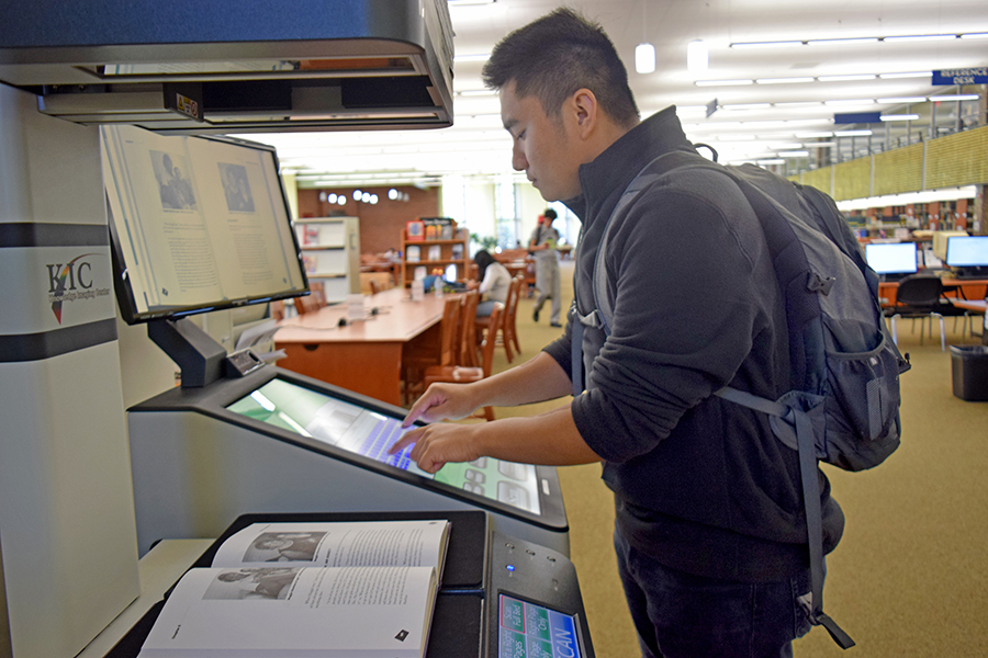 Sociology major Alfred Machacon scans a fibro- myalgia book on Thursday with the free scanner available for student use in the Library.