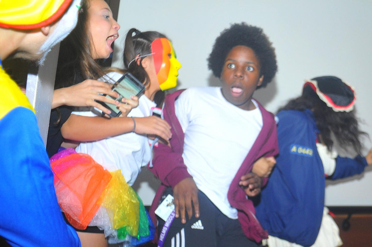 A group of students scream as they run past a scare spot during the free carnival scream house maze in the Knox Center on Tuesday.