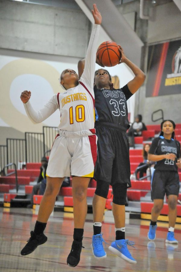 Comet guard Jameelah Hanif shoots over Mustang guard Elsa Ross in an attempt to end their offensive drought during Contra Costa College's 86-39 blowout loss at Los Medanos College on Friday.