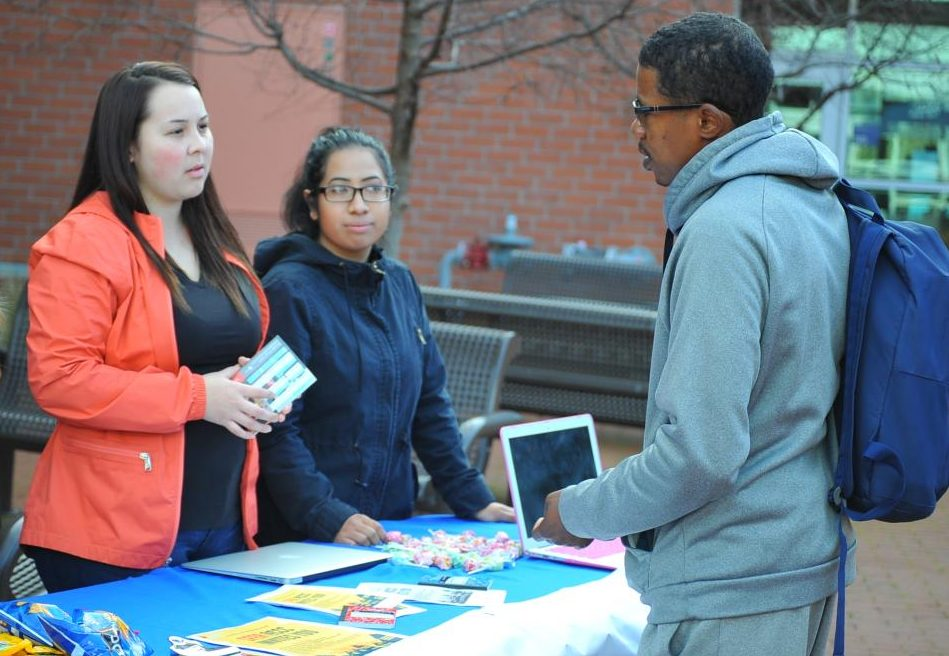 Psychology major Lizbeth Gonzalez (left) speaks to communications major Lionel Harris (right) about Students For Educational Reform during a tabling and informational meeting in the College Center Plaza on Monday.