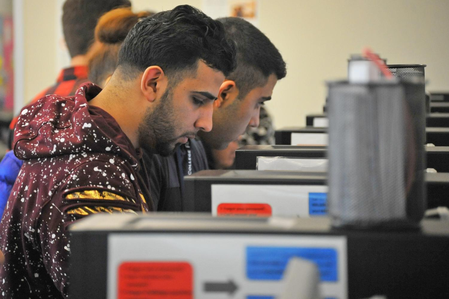 Richmond  resident Muhamed Alomari (front left) helps type his sisters' information on the online enrollment application on Jan. 22 in the Welcome Center in the Student Service Building. Over 2,000 Full Time Equivalent Students have enrolled in the 2018 spring semester according to the enrollment report of 2018.