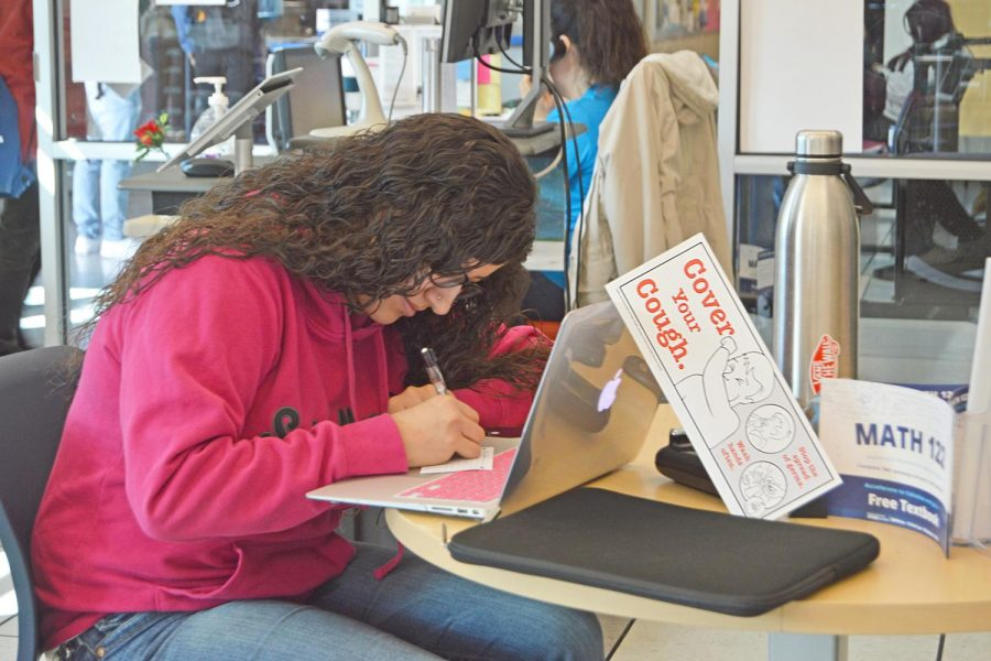 ABOVE:  A student works on her laptop as a CDC flier which recommends practicing effective flu precautions leans on it on Jan. 22.