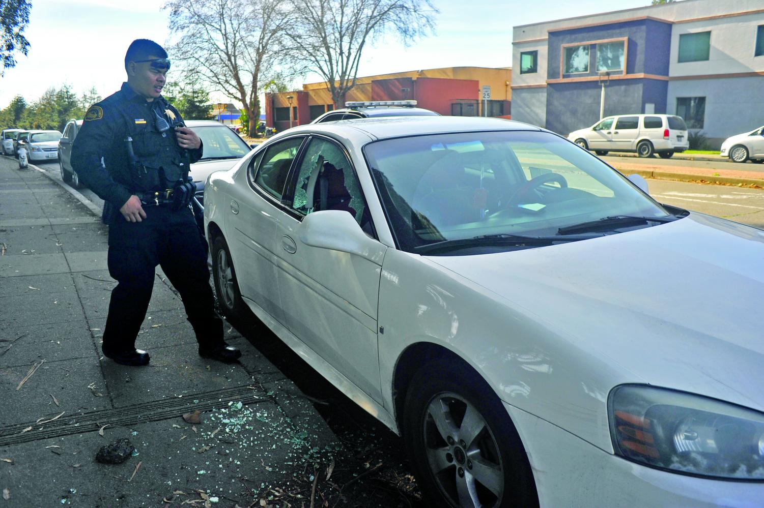 Contra Costa County Sheriff Deputy  Zunio  inspects   nursing major April Flanagan's car passenger window after it was shattered by a rock on Mission Bell Drive on Jan. 31.