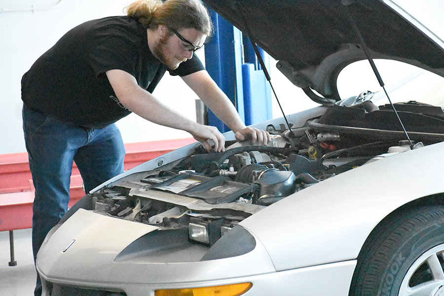 Automotive student Craig Yannow checks the fluid levels in the engine of his 1995 Camaro Z28 while in the automotive department in the CTC Building.