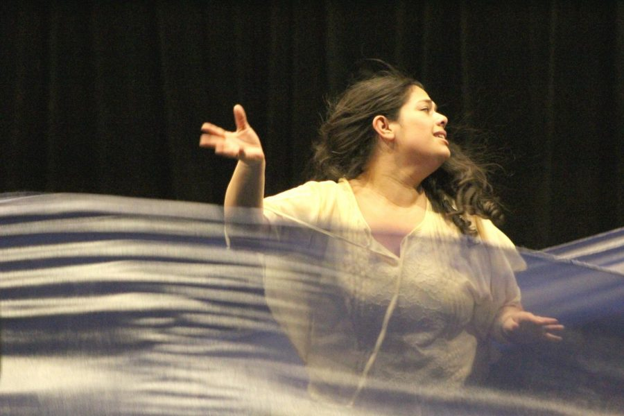 Xochiti, played by Stephanie Rivas, acts as she were being drowned with ribbons that signify water during a Monday rehearsal for