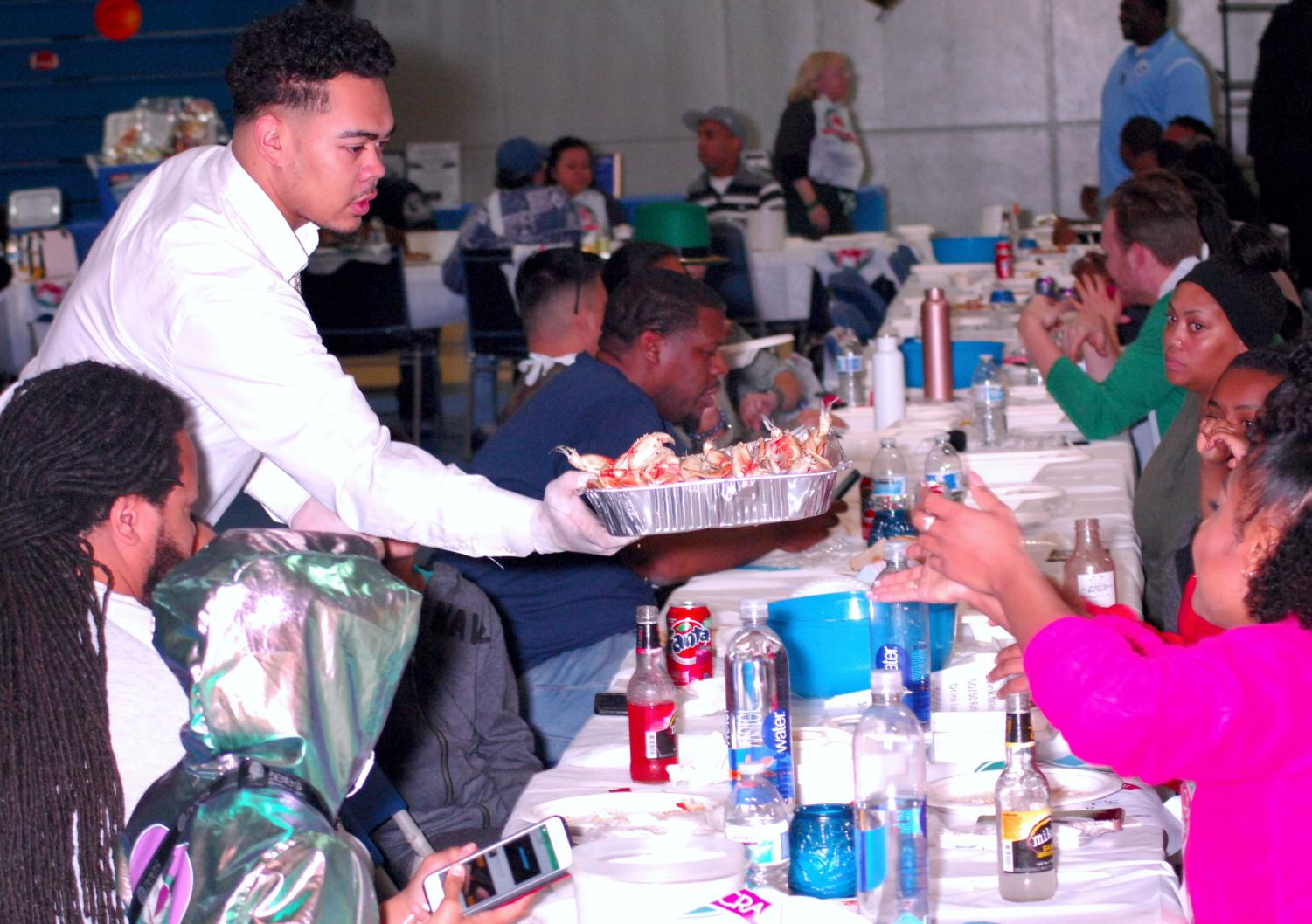 A student-athlete volunteer serves a platter of freshly cooked dungeness crab to a table of guests during the annual Crab Feed in the Gymnasium on Saturday.