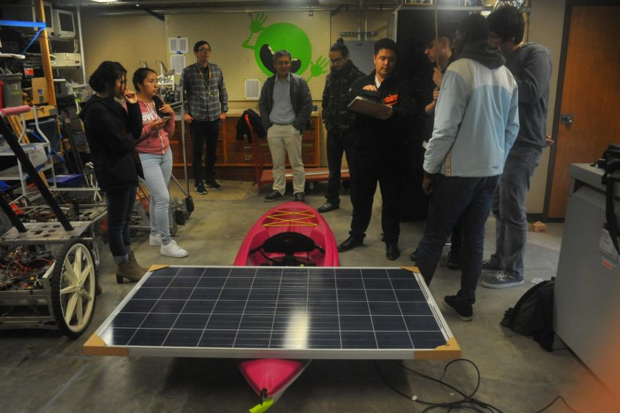 A group of students enrolled in Astronomy 298, Independent Study, inspect a kayak with a mounted solar panel during a meeting in the Art Building on April 6. The kayak will be raced in the Solar Regatta boat competition at Rancho Seco Recreational Lake on May 5.