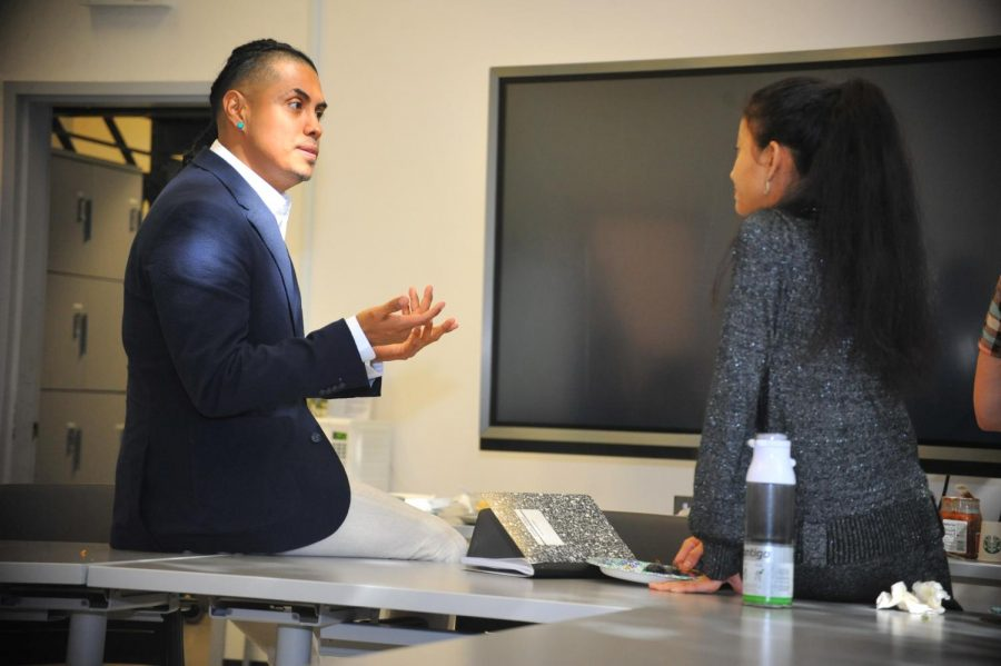 Contra Costa College alumnus Edwin Reyes (left) talks to physics major Ruth Elizabeth Whet (right) in the Physical Sciences Building after his Friday seminar.