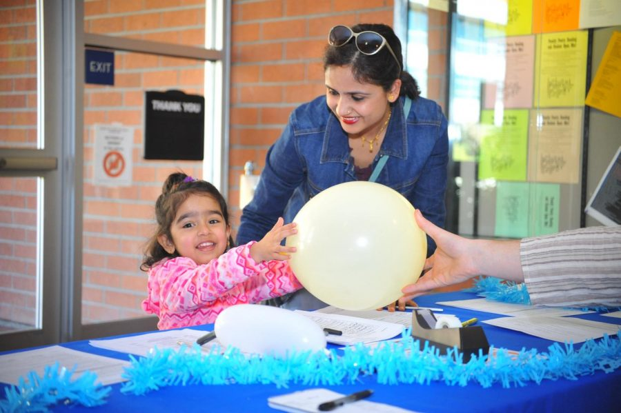 Debeshi Pantel (left) receives a balloon during the Teaching Café in the Library on Friday. Bantana Pantel (right) brought her daughter to the café to expose her to Contra Costa College and its community.