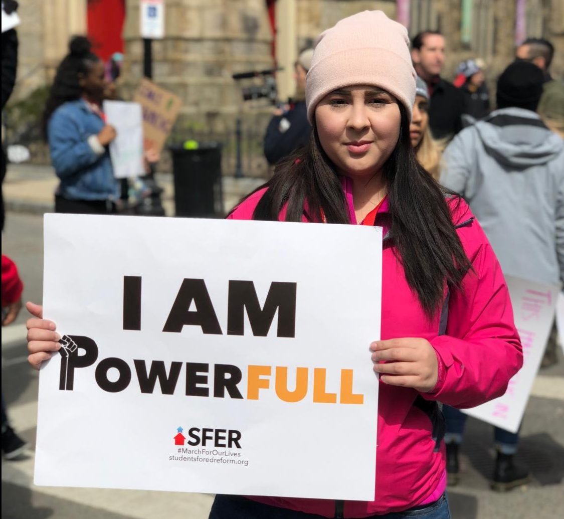 """La Raza studies major Lizbeth Gonzalez holds a sign during the """"March for Our Lives"""" action in Boston, Massachusetts on March 24."""