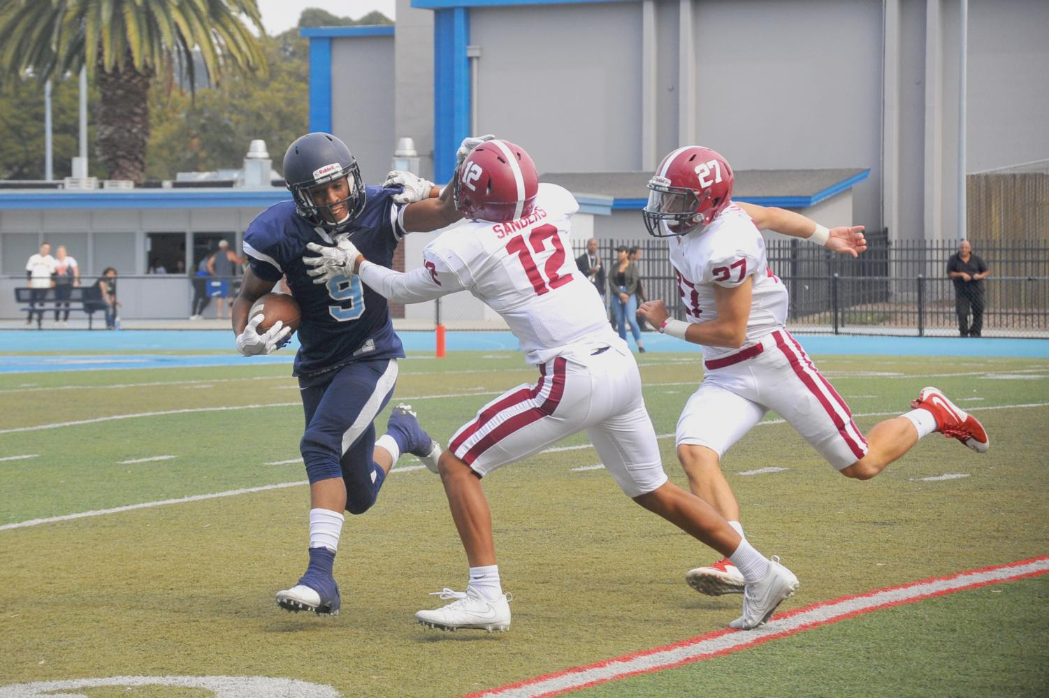 Comet wide receiver Courtney Beane (left) stiff arms Wolverine defensive back Dominick Sanders (middle) during  Sierra College's 56-28 win against Contra Costa College on Sept. 9 at Comet Stadium.