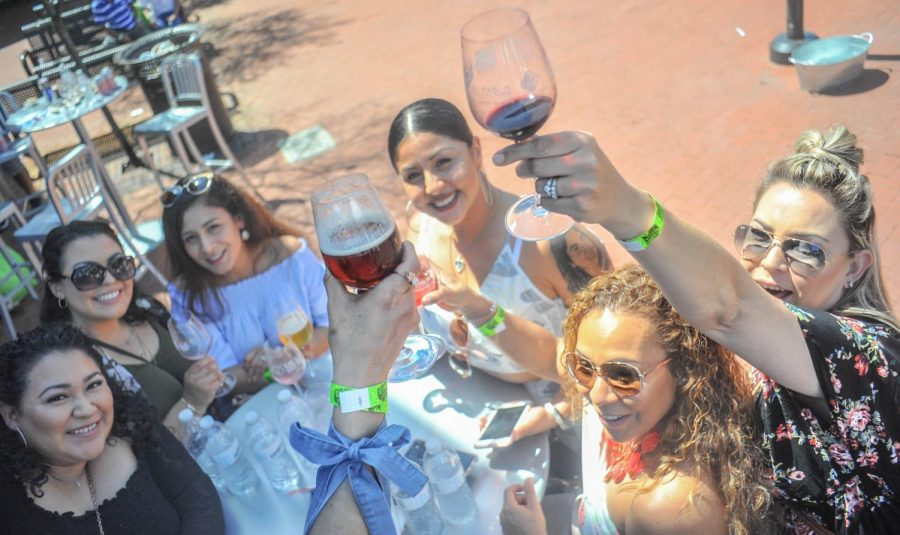 A group of female attendees raise their glasses as they cheer to a good time in the Campus Center Plaza during the Food & Wine event on Sunday.