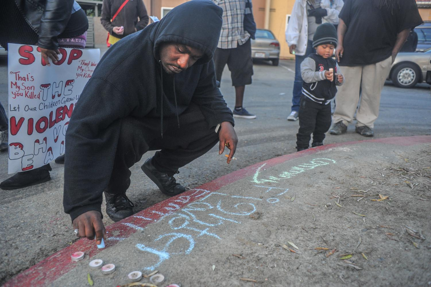 "Richmond resident Carnell Williams writes ""Fighter, Love, Family"" describing slain Richmond resident Mark Henderson II during a vigil for Henderson on Thursday near Crescent Park in Richmond."