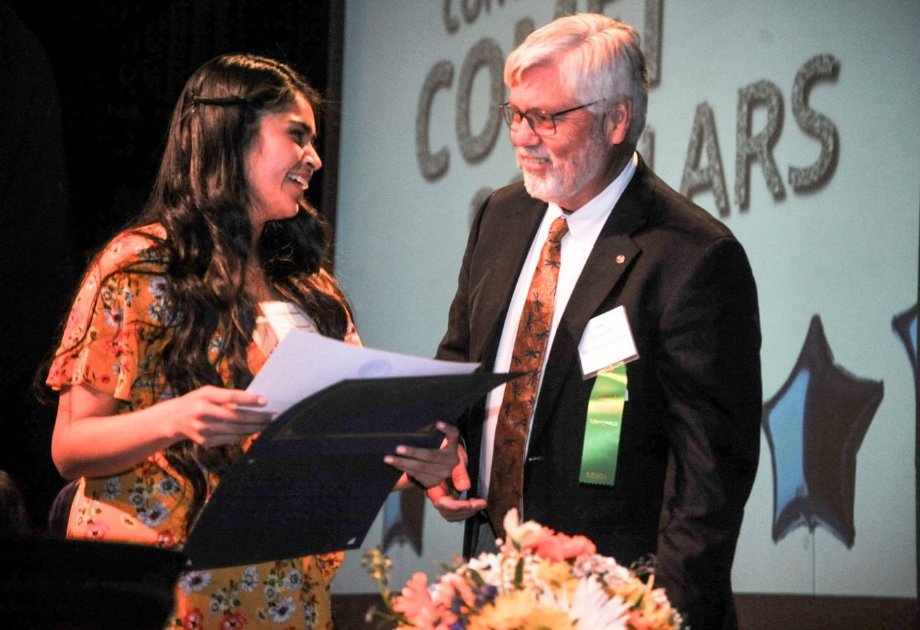 Josielyn Bustamante (left) receives a scholarship certificate from Foundation Secretary William van Dyk during the Scholarship Awards Ceremony in the Knox Center on May 2.