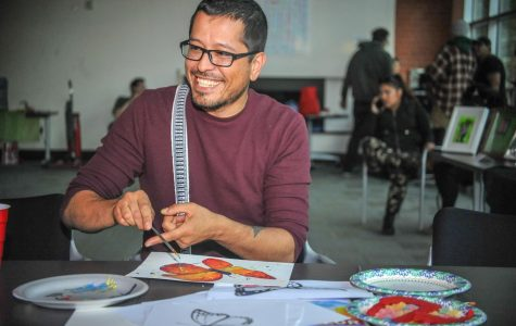 "La Raza studies professor Augustine Palacios paints a butterfly during the ""Exist to Resist"" art show in Fireside Hall on May 2."