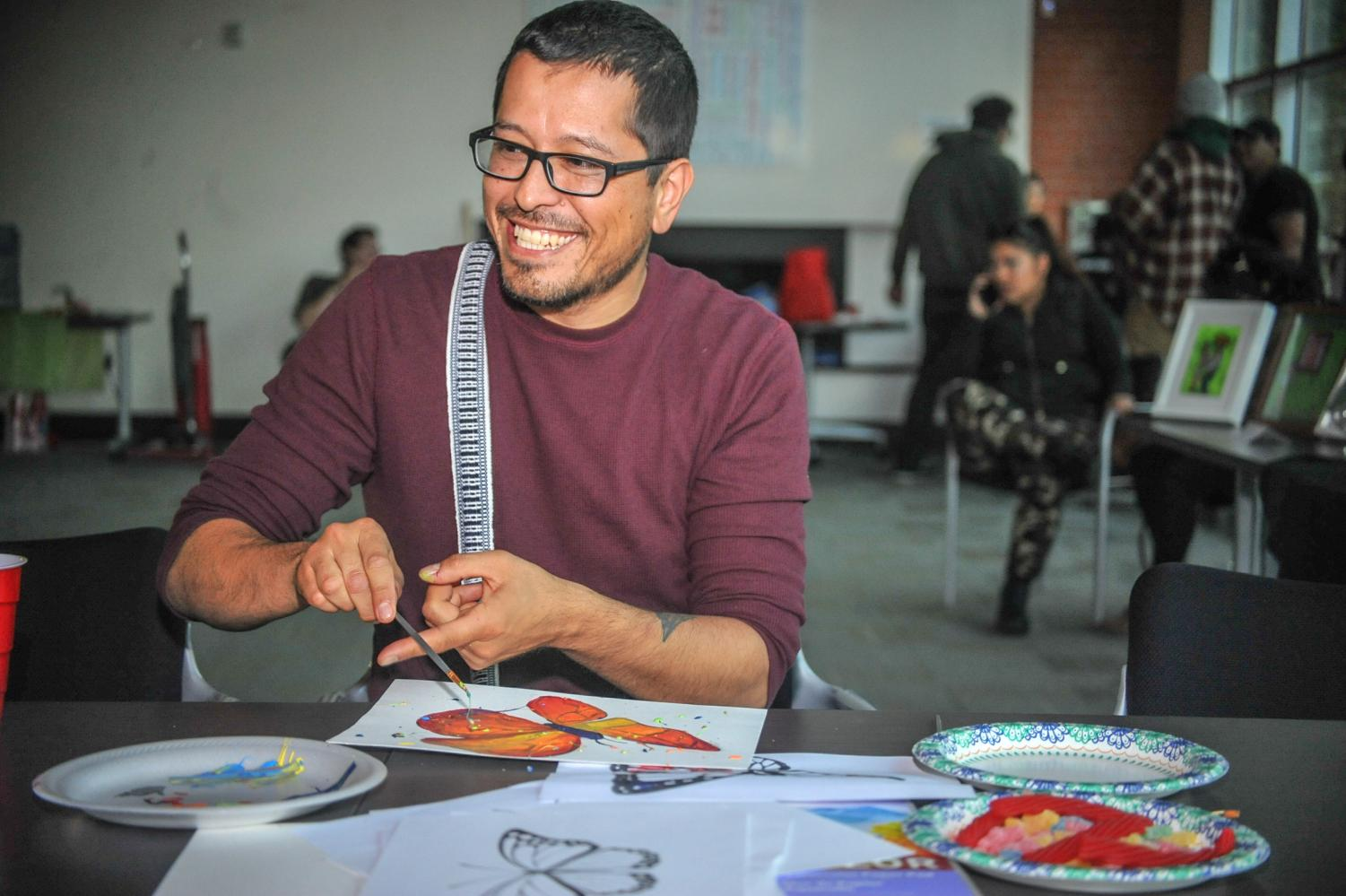 """La Raza studies professor Augustine Palacios paints a butterfly during the """"Exist to Resist"""" art show in Fireside Hall on May 2."""