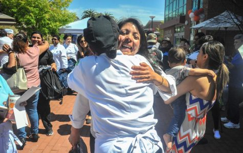 Culinary arts students hug each other after the announcement at the Food and Wine Event in the Campus Center Plaza of the seven students going to Italy. Every summer culinary arts students travel abroad to learn about Italian cuisine.