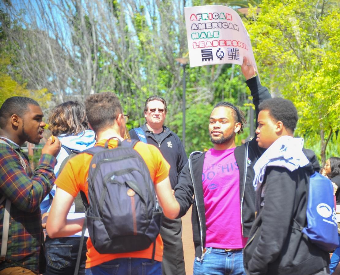 African-American studies major Elijah Morgan raises a sign to gather high school seniors for a tour of the African-American Male Leadership group during Comet Senior Day in the Campus Center Plaza on Thursday.