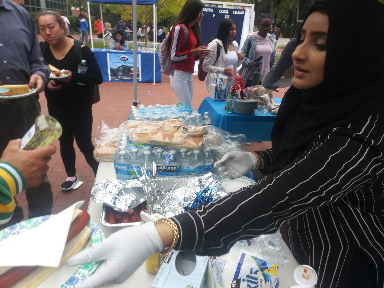 Liberal arts major Aber Mudhish hands out a hot dog  to eager students during Welcome Week on Aug. 28.