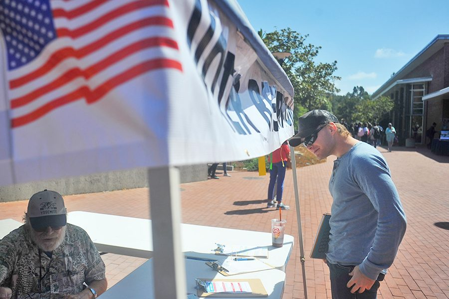 Criminal justice major Ben Hayunga peeks into one of the many voter registration booths stationed around the campus during the Constitution Day event held in the Campus Center Plaza.