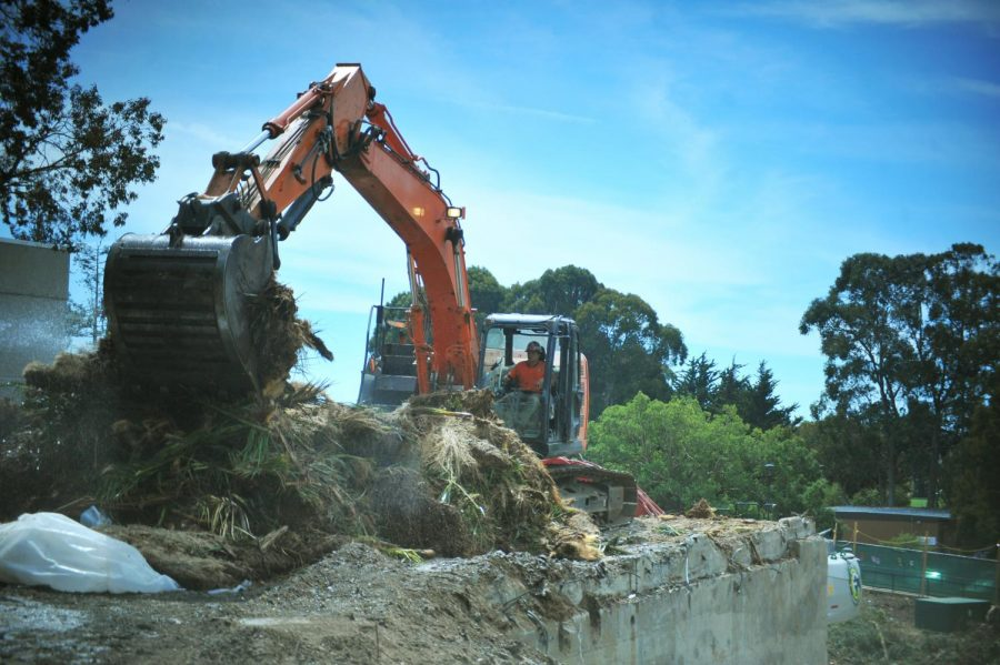 An excavator operator halls debris from one area to another during the demolition of the Health Services Building on Sept. 12