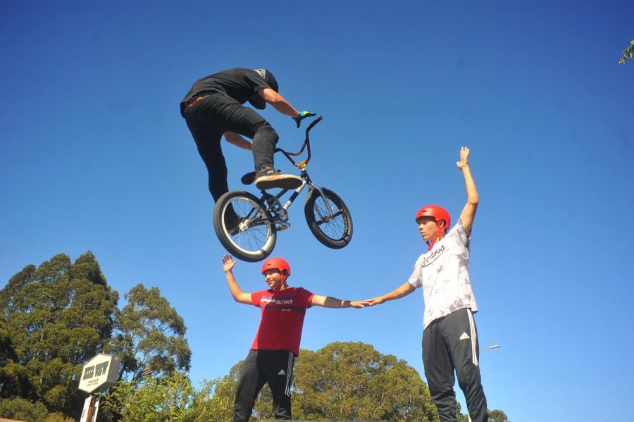 An Air Time Action Sport cyclist jumps over two boys as part of a performance during El Sobrante Stroll on Sunday.