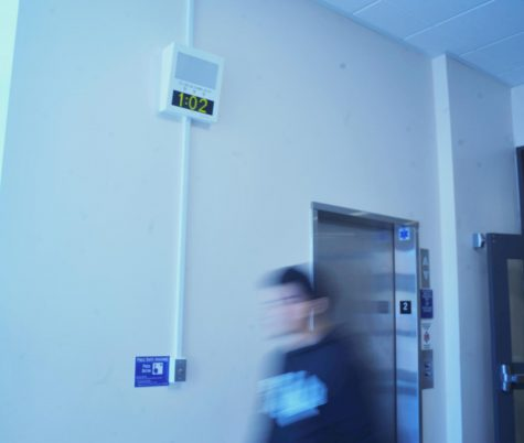A student walks past one of the campuswide alert system boxes set up in the hallway of the second floor of the General Education Building.