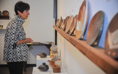 Antioch resident Cynthia Jameson looks at ceramic plates created by ceramics professor  Mary Law  and six of her students in the Art Building on Sept. 6.