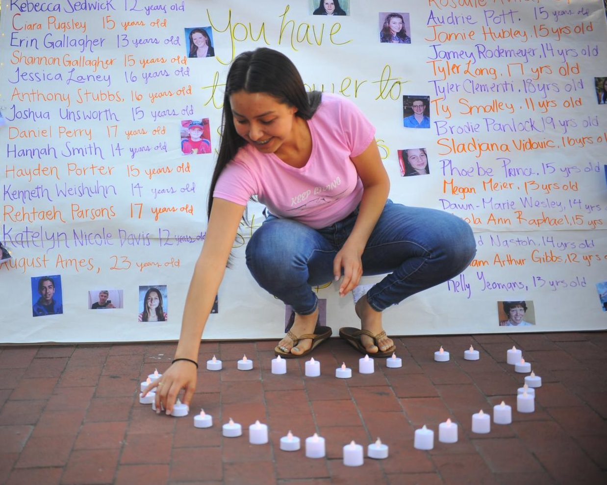 Middle College High School senior Noemi Gomez puts candles in the shape of a heart during Suicide Prevention Week at Contra Costa College.