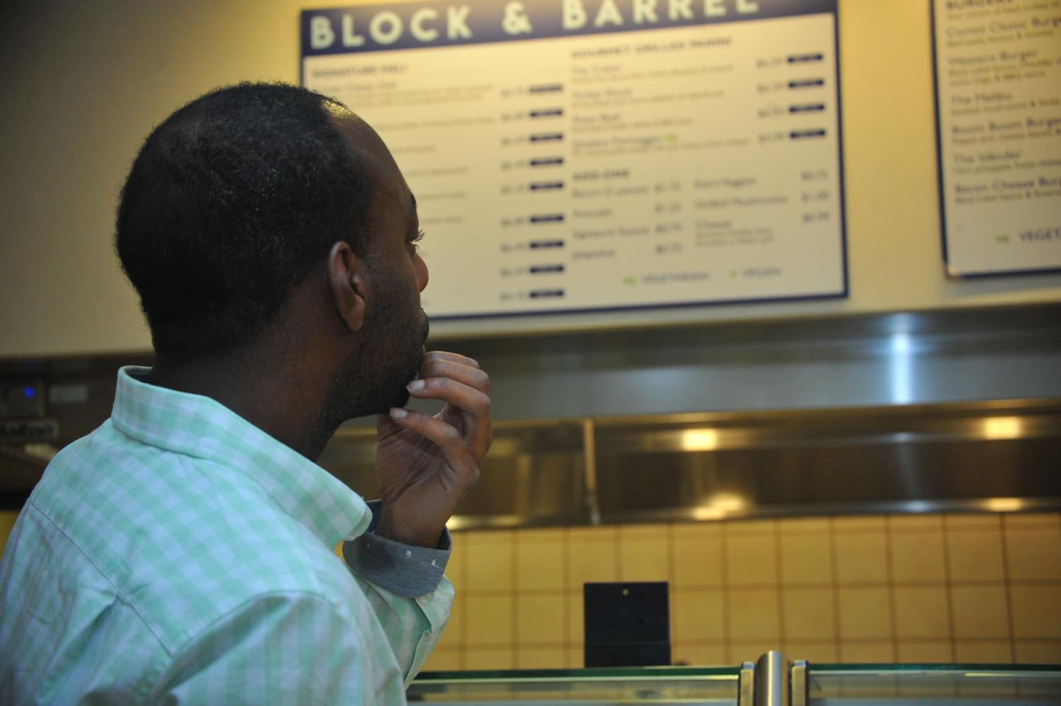 A student looks at the menu before  ordering at Brix cafe on Wednesday.