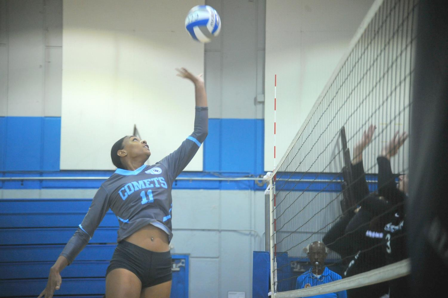 Comet middle blocker Makaya Thomas hits the ball over the net in Friday's loss against College of Alameda in the Gymnasium.