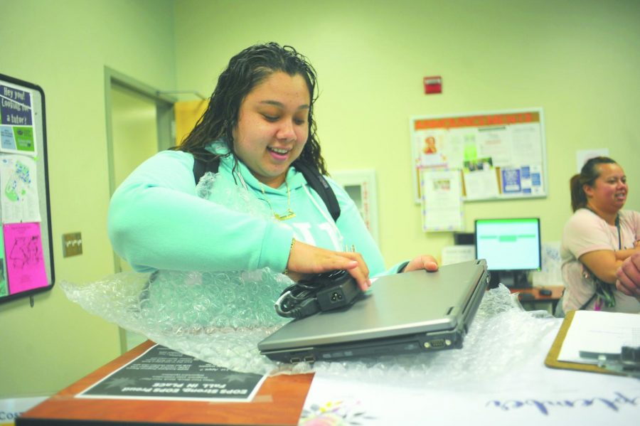 Medical assisting major  Cynthia Hernandez  unwraps a free Dell laptop computer given to her as part of the CalWORKs program on Sept. 26 in SSC-106.
