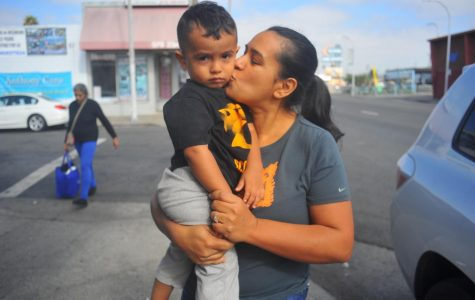 Guadalupe Mendoza kisses her son, Joshua Mendoza as she walks down 23rd Street in Richmond, California on Monday.