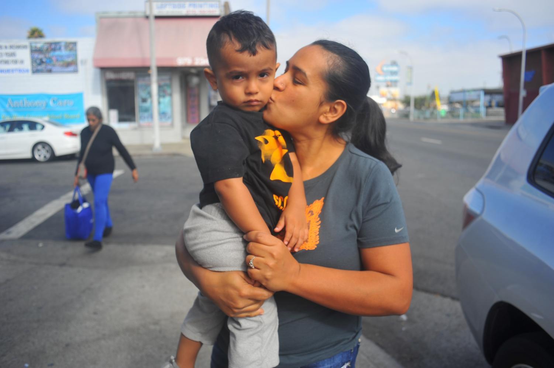 Guadalupe Mendoza kisses her son, Joshua Mendoza as she walks down 23rd Street in Richmond, California on Monday.
