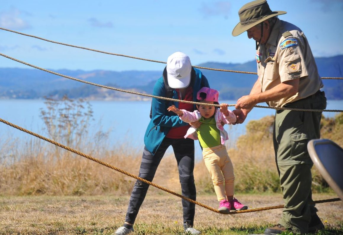 Scout master Fred Stevens helps a mother hold her daughter as she walks across an obstacle course set up by the Boy Scouts of America at the North Richmond Shoreline Festival in Point Pinole on Saturday.