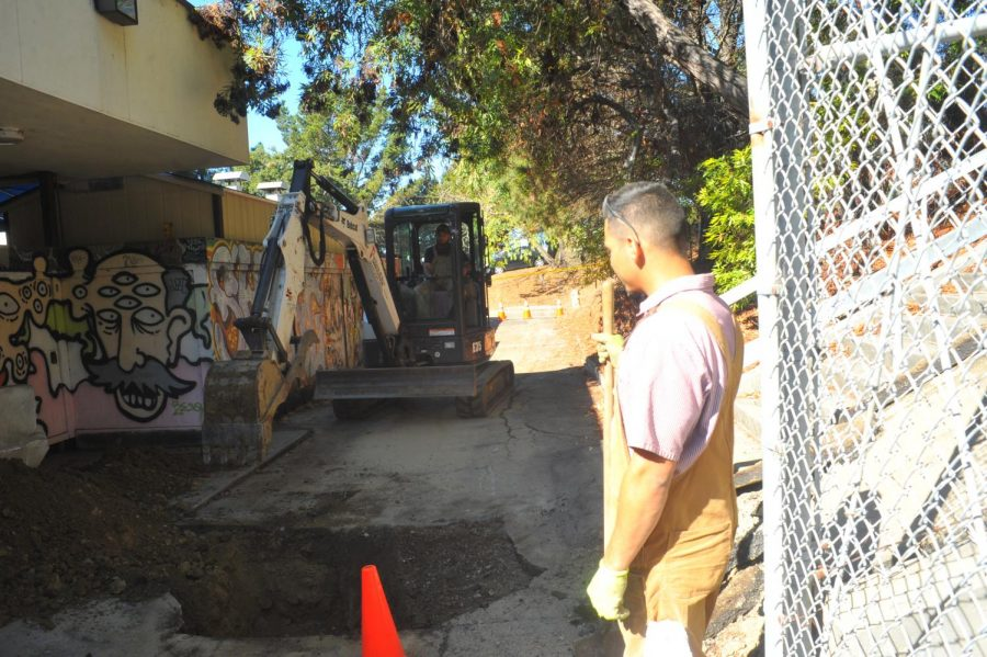 Plumbers Martin Campos (left) and Geovany Melendez (right) dig a 4-foot deep trench to repair the broken water pipe behind the Art Building on Monday.