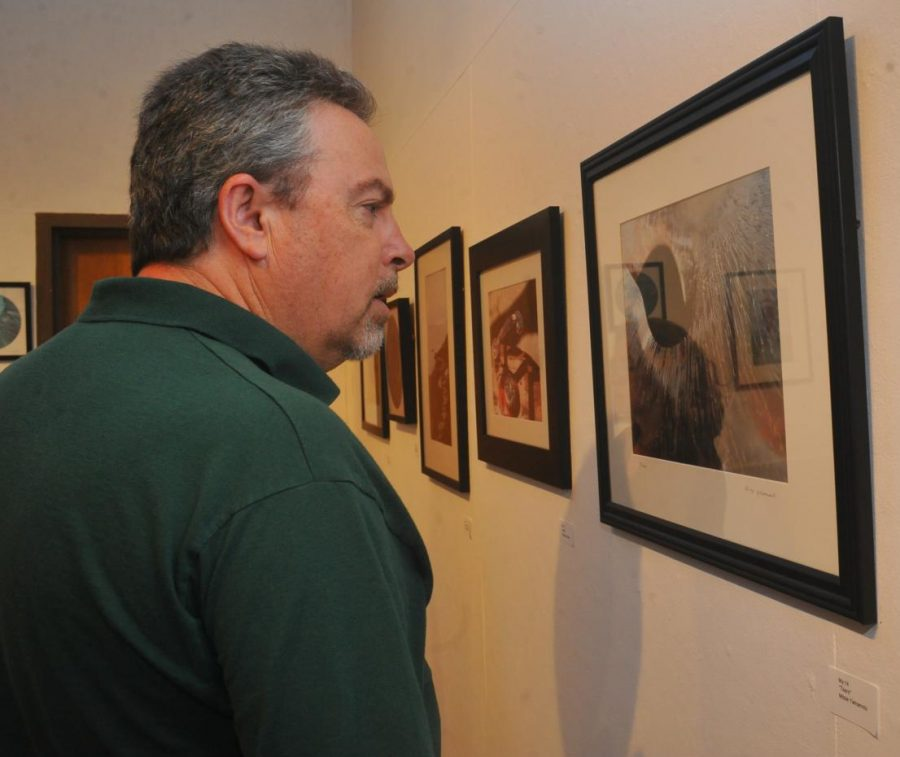 Union City resident John Lacabanne views photography by his sister Lisa Lacabanne in the Eddie Rhodes Gallery Oct. 17.