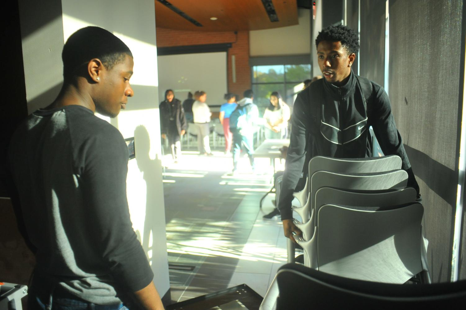 Students put away tables after the student town hall event finished early because of the lack of administrative participation in the Fireside Hall on Thursday.