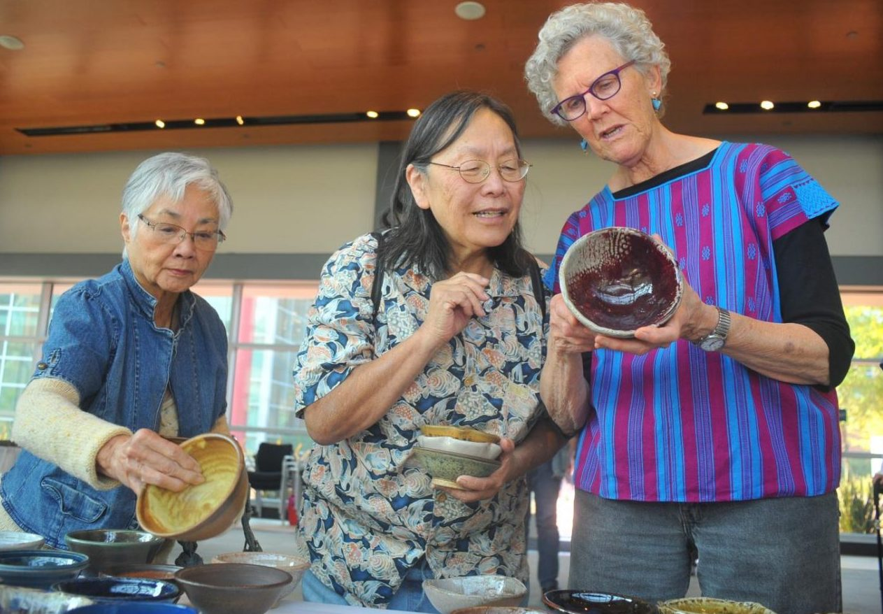 Ceramics instructor Mary Law (right) shows off a ceramic bowl to art majors Barbara Burgess (left) and Grace Brown at Fireside Hall.
