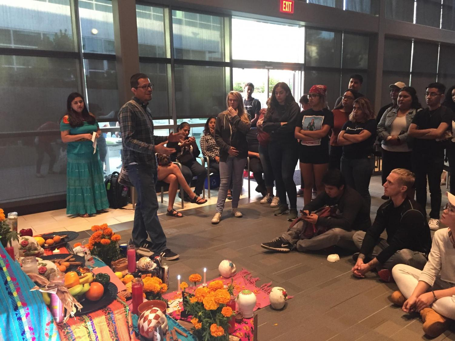 La Raza studies professor Augustin Palacios speaks to the crowd at the Dia de los Muertos event in Fireside Hall on Thursday.