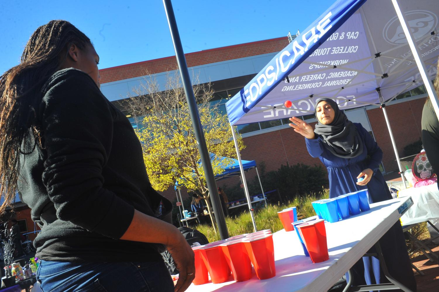 Student Malekah Isa (right) plays soda pong during Club Rush in the Campus Center Plaza on Oct. 31.