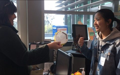 A student receives an N95 mask in the Welcome Center on Thursday.
