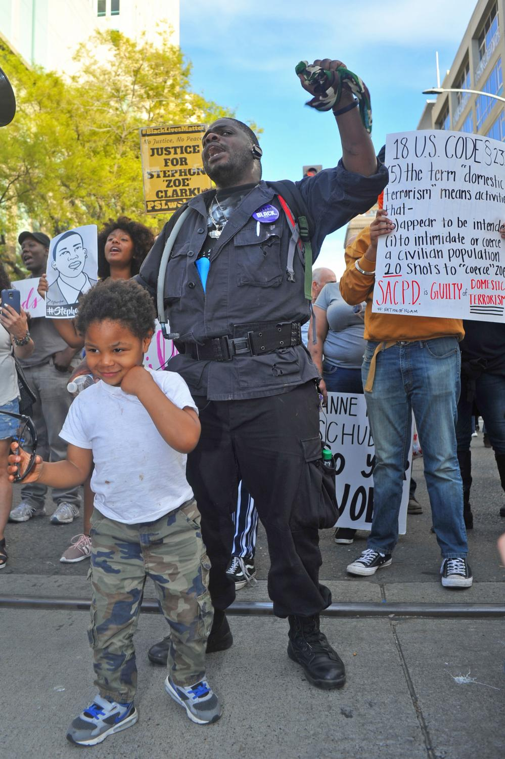 Sacramento resident Darnell Canfield (middle) and his son chant in front of a protest line in downtown Sacramento, California.