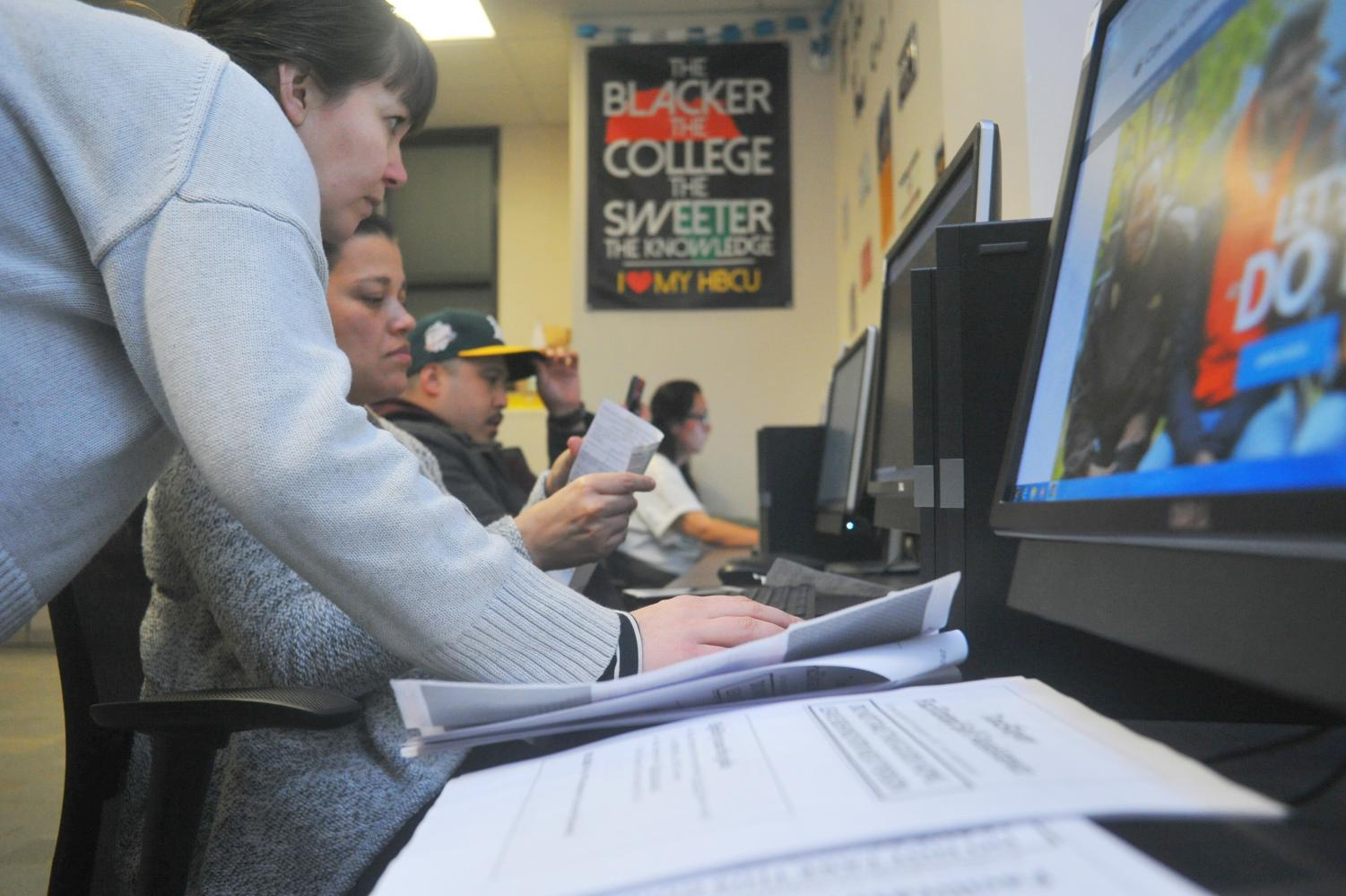 Colleen Smallfield (left) helps nursing major Maria Caroache (right) at the tax preparation workshop at the Transfer/Career Center Friday.