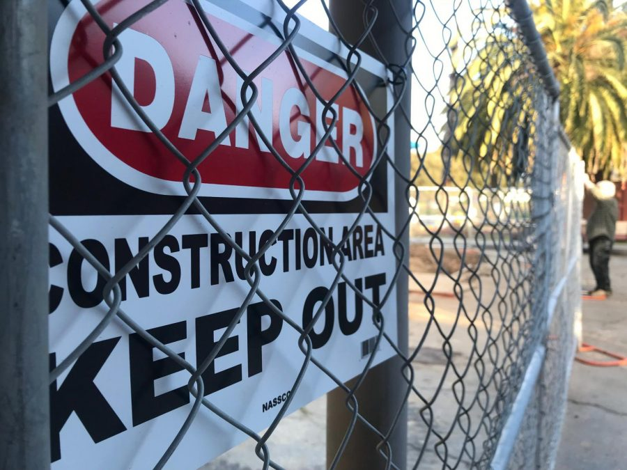 A+construction+worker+locks+the+fence+surrounding+the+Gymnasium+for+renovations.