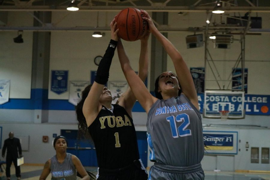 Comet forward Larissa Carvalho goes up for a shot as she is contested by 49er Gloria Leon-Campos during Contra Costa College's 64-57 loss to Yuba College on Feb. 20 in the Gymnasium.