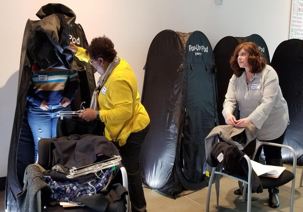 Volunteers Renne Parson (left) helps a student (right) change into an outfit as Maria Giron (right) organizes clothes during the Steps to Stability event on Friday in Fireside Hall.