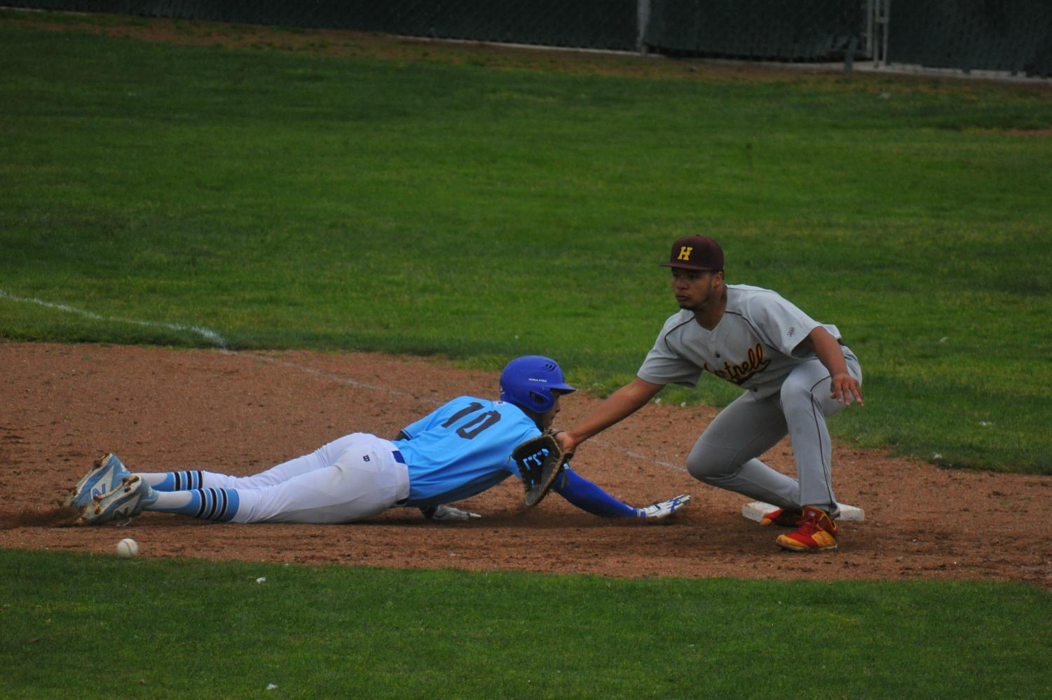 Hartnell College first baseman Chris Wright fields a pickoff throw from his pitcher as Comet outfielder Mychael Jamison dives safely back to first base.