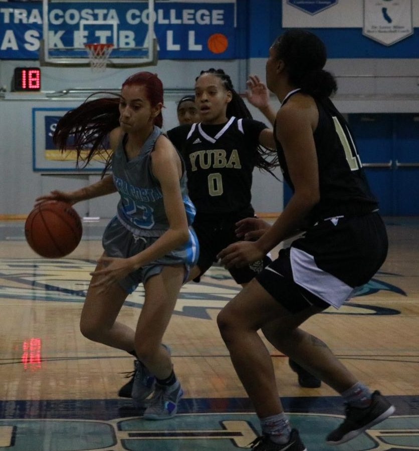 Sophomore guard Victoria  Lopez dribbles through two Yuba College guards, LaiLani Hanks and Taeyla Washington, during a game at the Gymnasium on Feb. 20.