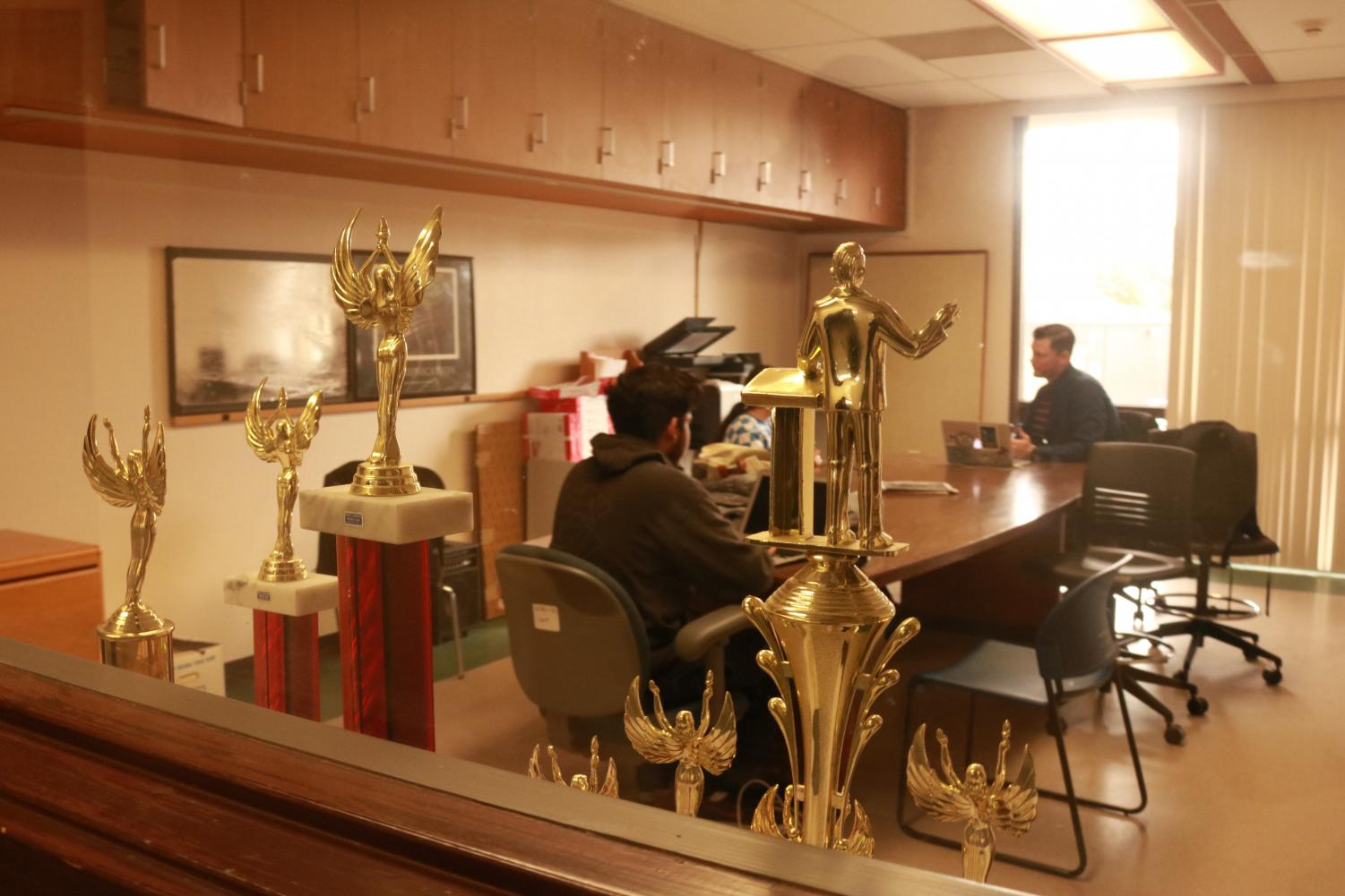 Speech team captain Shreejal Luitel (center) and team member Gaby Hernandez (hidden behind trophy) meet with coach Randy Carver (right) in the Speech Lab in AA-219.